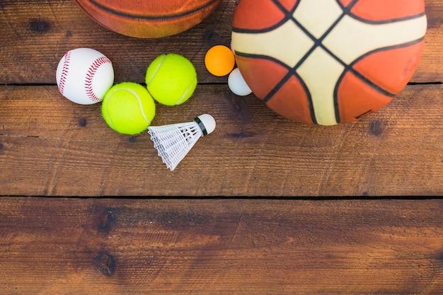 Ping-pong ball; baseball; shuttlecock; basketball and tennis ball on wooden plank