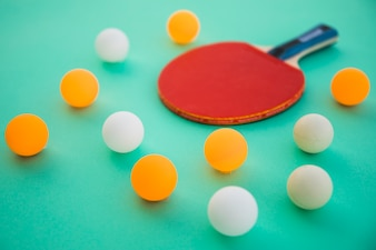 Ping pong balls and wooden racket on turquoise background