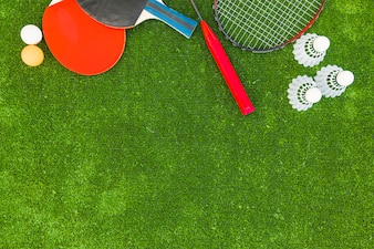 Ping-pong balls; shuttlecocks; badminton and rackets on green turf