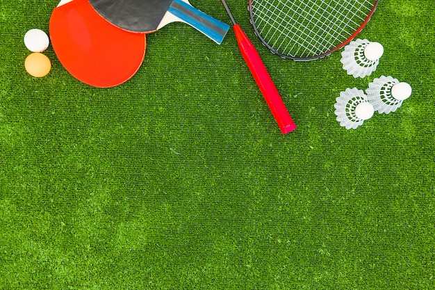 Ping-pong balls; shuttlecocks; badminton and rackets on green turf