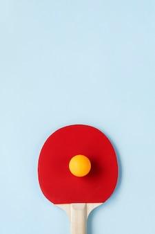 탁구 패들과 밝은 파란색 배경에 공