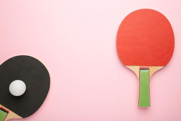 Ракетки для пинг-понга и мяч на розовом фоне. вид сверху