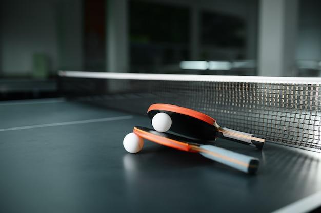 Ping pong rackets and ball at the net closeup