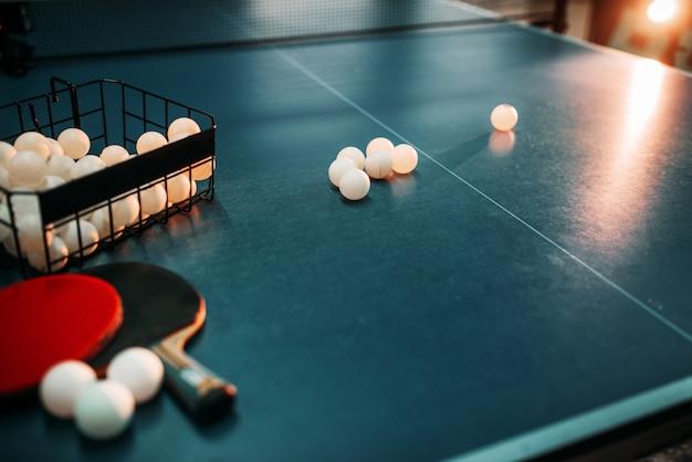 Стол для пинг-понга, ракетки и корзина с шариками крупным планом