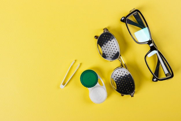 Pinhole glasses, lenses with container and glasses for sight.