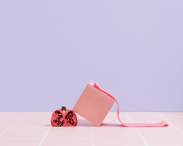 ピンクの3dキューブ、ザクロ、パステルパープルの背景にフィットネスゴムバンド。ホームまたはジムのトレーニングの概念。健康的なライフスタイルシーン。最小限のスポーツ用品の写真。