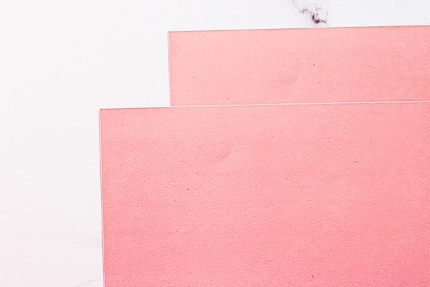 Розовые бумаги на белом мраморном фоне в виде офисных канцелярских принадлежностей, роскошных брендов, плоских ...