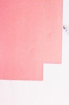 Розовый лист бумаги на белом мраморном фоне в виде офисных канцелярских принадлежностей, роскошный брендовый плоский дизайн и дизайн фирменного стиля для макетов