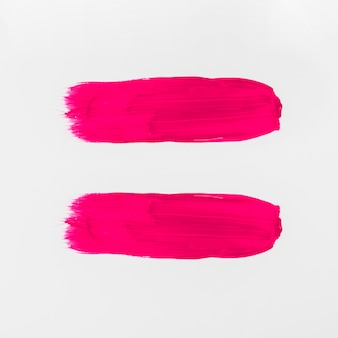 Pink abstract watercolor brush strokes on white background