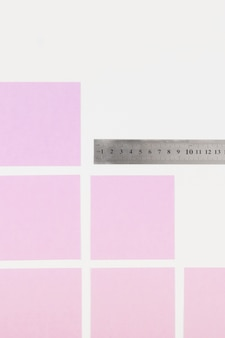 Pink adhesive notes and ruler on white background