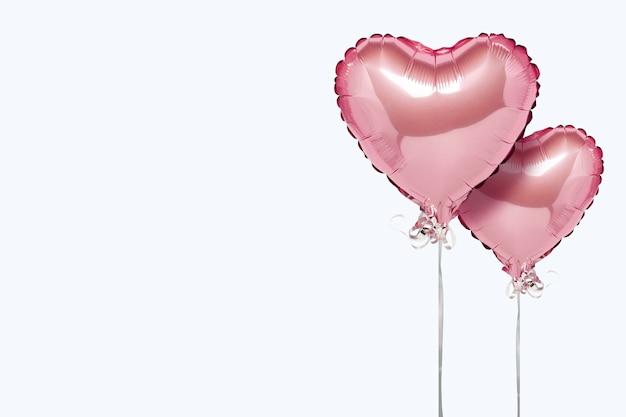 흰색 표면에 분홍색 공기 풍선 심장 모양