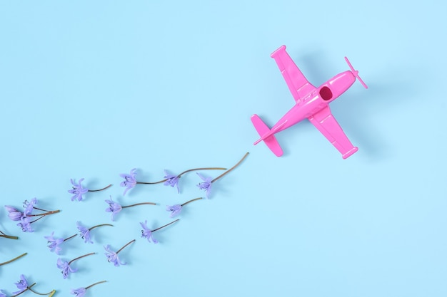 Pink airplane takes into a sharp turn on blue background