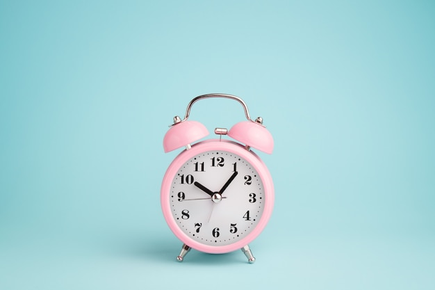 Pink alarm clock on blue