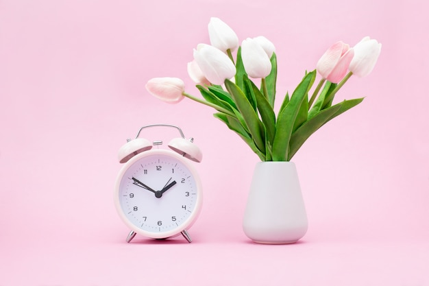 Pink alarm clock and a bouquet of flowers on pink