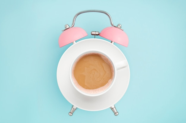 Pink alarm clock and coffee cup on blue . breakfast time . minimal style