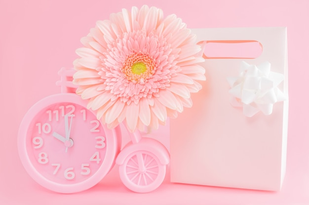 Pink alarm clock, gift box and gerbera flower