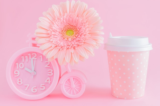 Pink alarm clock, glass of coffee take-away and gerbera flower on pink background.