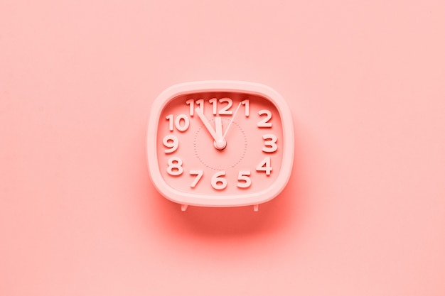 Pink alarm clock lying on yellow surface background. trendy living coral color of year 2019.top view.