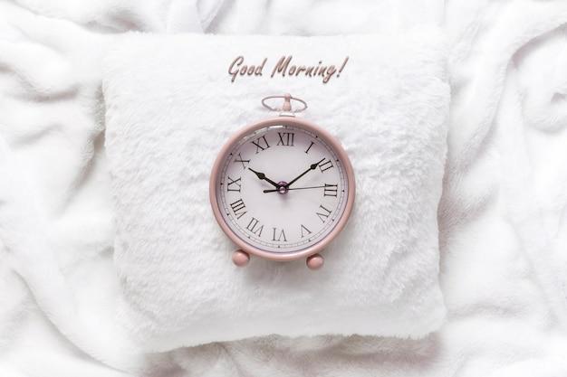 白い毛布の白い枕にピンクの目覚まし時計。