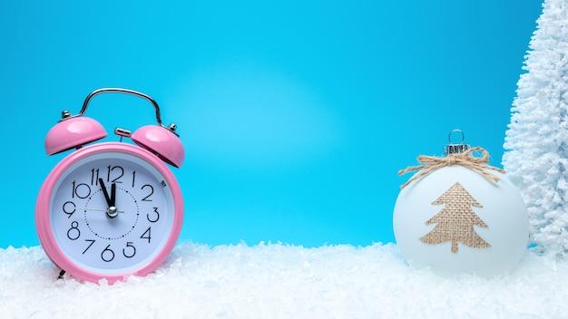 地球と雪の上のピンクの目覚まし時計