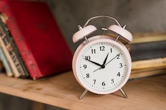 木製の本棚にピンクの目覚まし時計