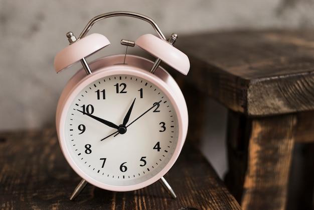 Розовый будильник на деревянном столе