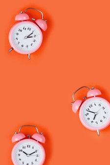 Розовый будильник на желтом фоне.