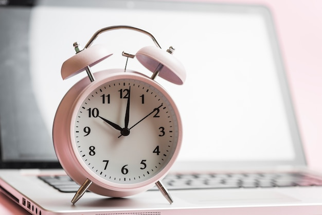 Pink alarm clock showing the time 10'oclock on laptop