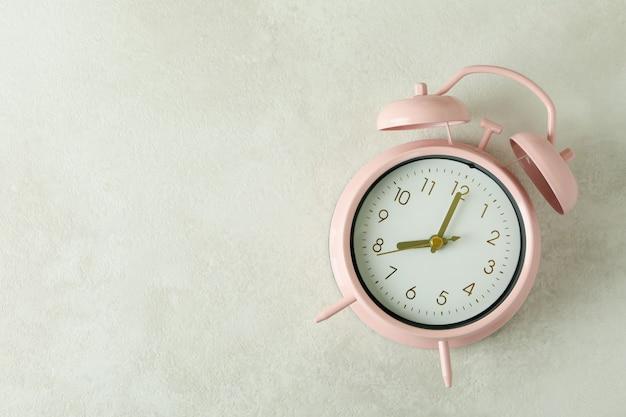 Pink alarm clock on white textured background