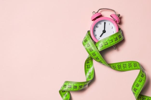 Розовый будильник с зеленой измерительной лентой, вид сверху, копией пространства.