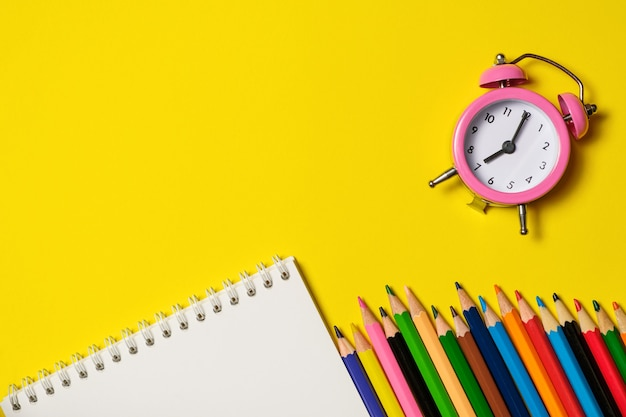Розовый будильник с канцелярскими товарами на желтом фоне.