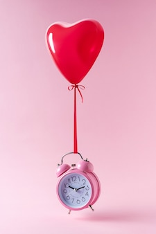 赤いハート型の風船とピンクの目覚まし時計