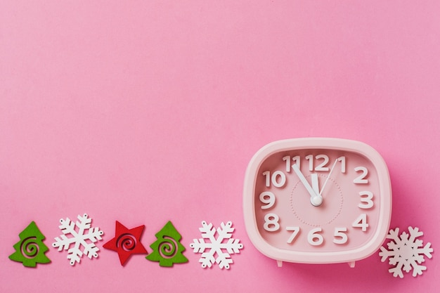Pink alarm clock with toys and snowflakes lying on pink surface background. new year or christmas concept. top view. cope space.