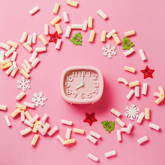 Pink alarm clock with toys and snowflakes lying on pink surface. new year or christmas concept. top view. cope space.square image.