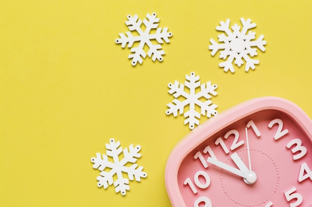 Pink alarm clock with toys and snowflakes lying on yellow surface background. new year or christmas concept. top view. cope space.