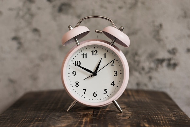 Pink alarm clock on wooden desk against weathered wall