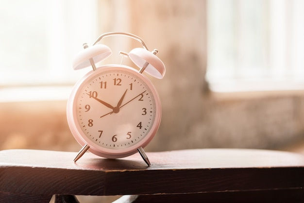 Pink alarm clock on wooden table in sunlight