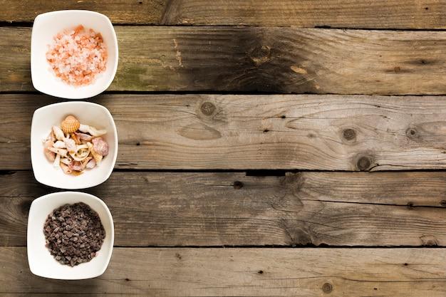 Розовая и черная соль с морскими раковинами в миске на деревянном столе