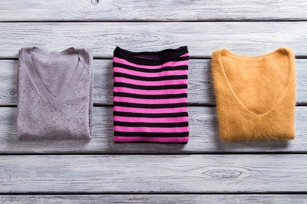 핑크와 블랙 스트라이프 풀오버. 회색 나무 바탕에 스웨터입니다. 이번 가을에는 무엇을 입을까. 고품질 상품만.