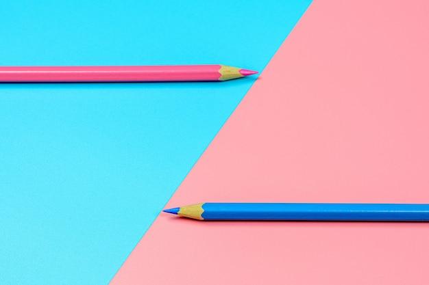 青とピンクの背景にピンクとブルーのクレヨン鉛筆。