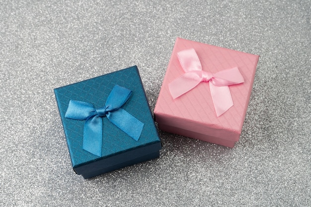 Розовые и синие подарочные коробки с бантом на фоне блеска.