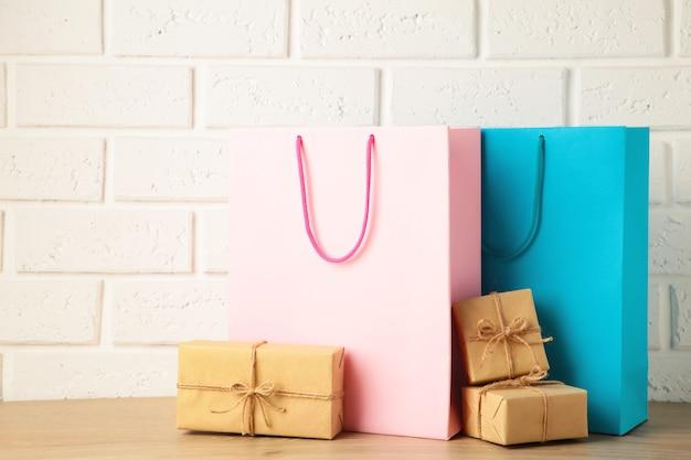 明るい背景にギフトとピンクとブルーのショッピングバッグ。ブラックフライデー。上面図