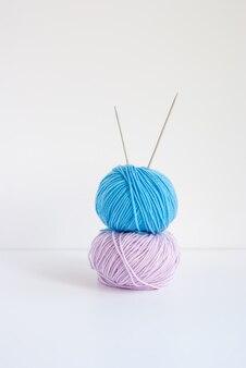 아기 원사의 핑크와 블루 skeins 및 흰색 배경에 뜨개질을위한 두 바늘