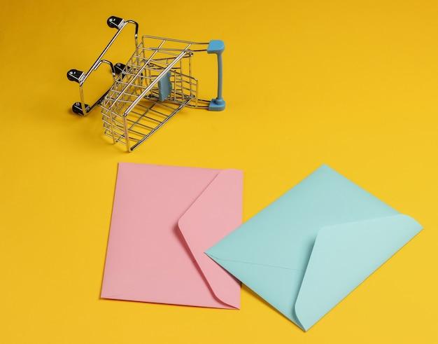 Розовый и синий два конверта и тележка для покупок на желтом фоне. мокап на день святого валентина, свадьбу или день рождения
