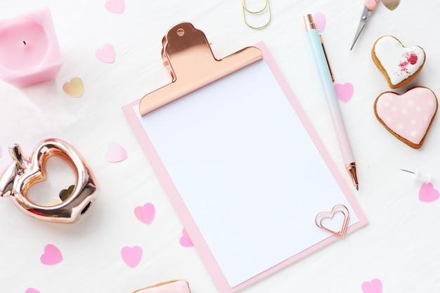 ピンクとゴールドのクリップボード、ペン、ジンジャーブレッドのハート、キャンドル、金色のリンゴ、ペーパークリップ、白いテーブルに紙吹雪の心。ホームオフィスのコンセプトです。