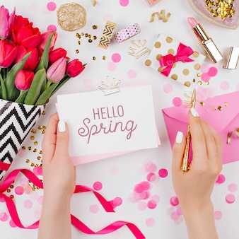 花柄のピンクとゴールドスタイルのデスク。女性の手はカードを保持します