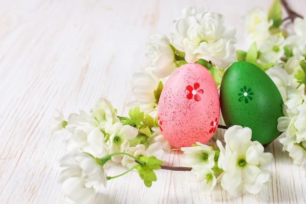 짚 둥지 및 지점에 분홍색과 녹색 부활절 달걀