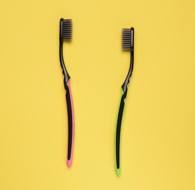 Розовые и зеленые пластиковые зубные щетки на желтом фоне, вид сверху