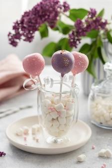 ピンクとライラックのケーキが、花束の壁にマシュマロと一緒にグラスに飛び出します。誕生日、結婚式、休日のコンセプトです。垂直画像。