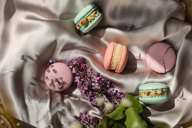 ピンクとミントのフレンチマカロンまたはマカロンクッキーと布の背景にライラックの花。ナチュラルフルーツとベリーのフレーバー、バレンタインデーのイースターのためのクリーミーな詰め物と愛の食べ物。